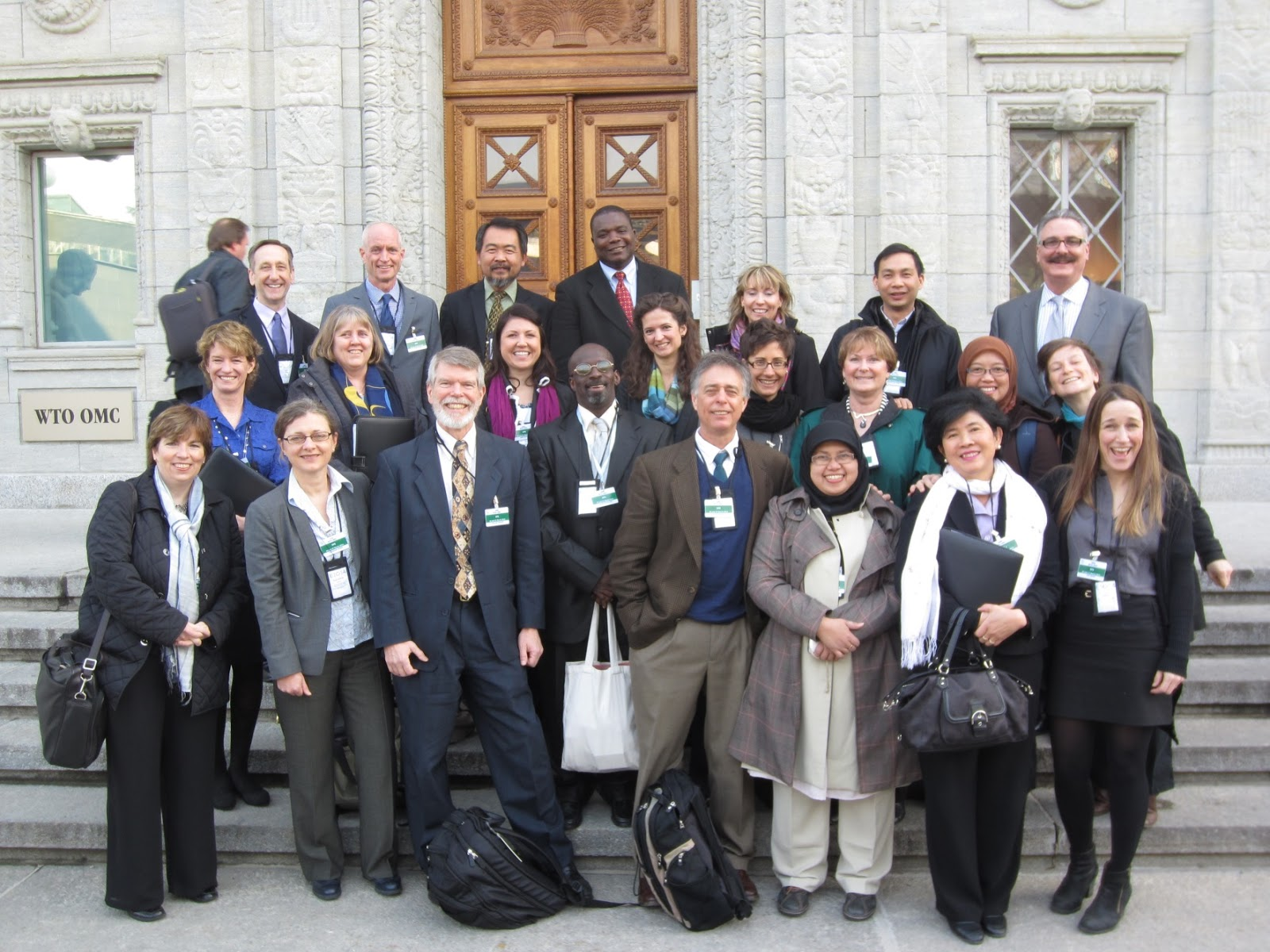 Full group of 2014 EIO participants standing on the steps of the WTO building