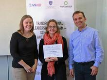 UMN faculty Karin Hamilton and University of Prishtina faculty giving certificate to Prishtina student